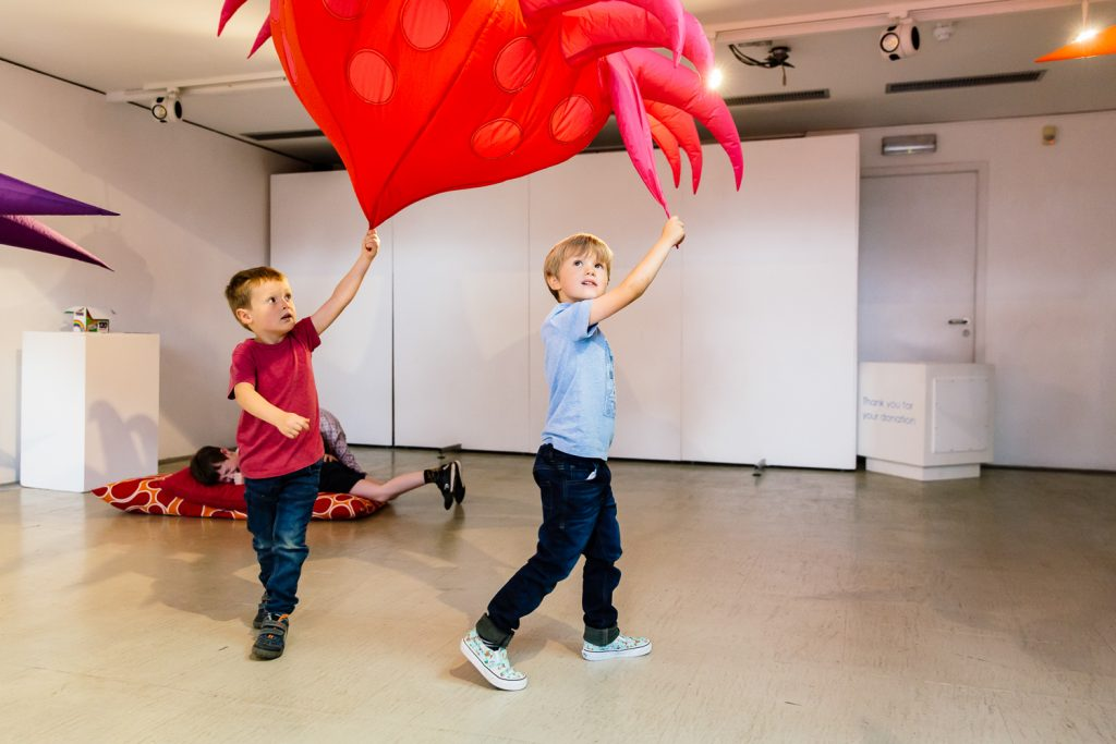 Two young boys play with inflatable coloured microbes at an exhibition at The Point in Doncaster