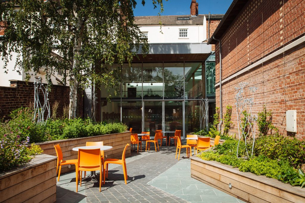 A beautiful garden space with orange chairs to have a drink or some food from the cafe at The Point, Doncaster
