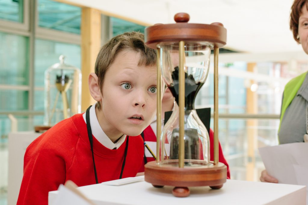 Boy looks amazed at a large sand timer in the gallery at The Point in Doncaster