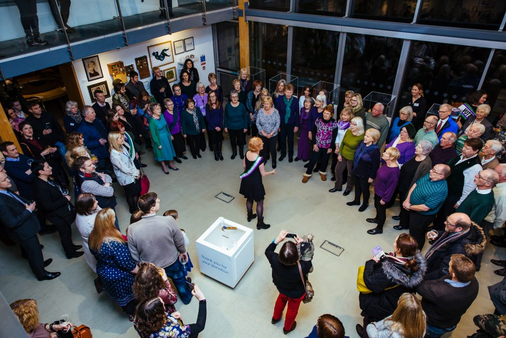 A large group of Quirky Choir members stand in a circle to sing songs as part of the Rebel Daughters launch at The Point in Doncaster
