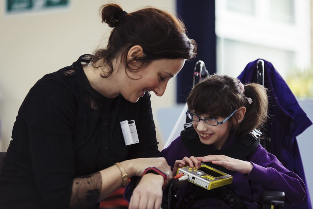 A young girl in a wheelchair plays a synthesizer as part of an All Aboard session in school
