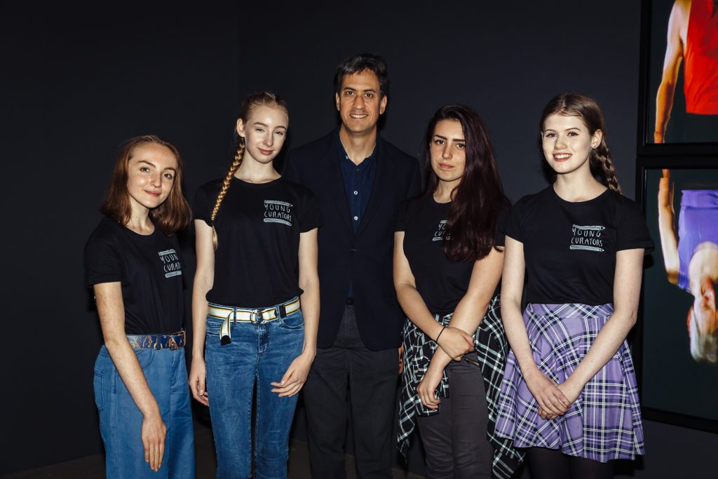 A group of young people with Young Curators tshirts stand with Ed Miliband MP at The Point in Doncaster