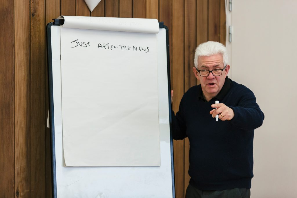 Poet Ian McMillan pointing next to a whiteboard at a Singing for Memory workshop in Doncaster.