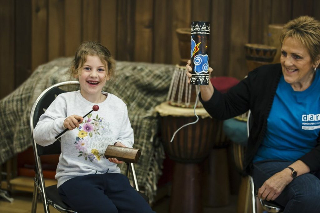 young participant and volunteer playing instruments at a darts in Doncaster workshop at The Point