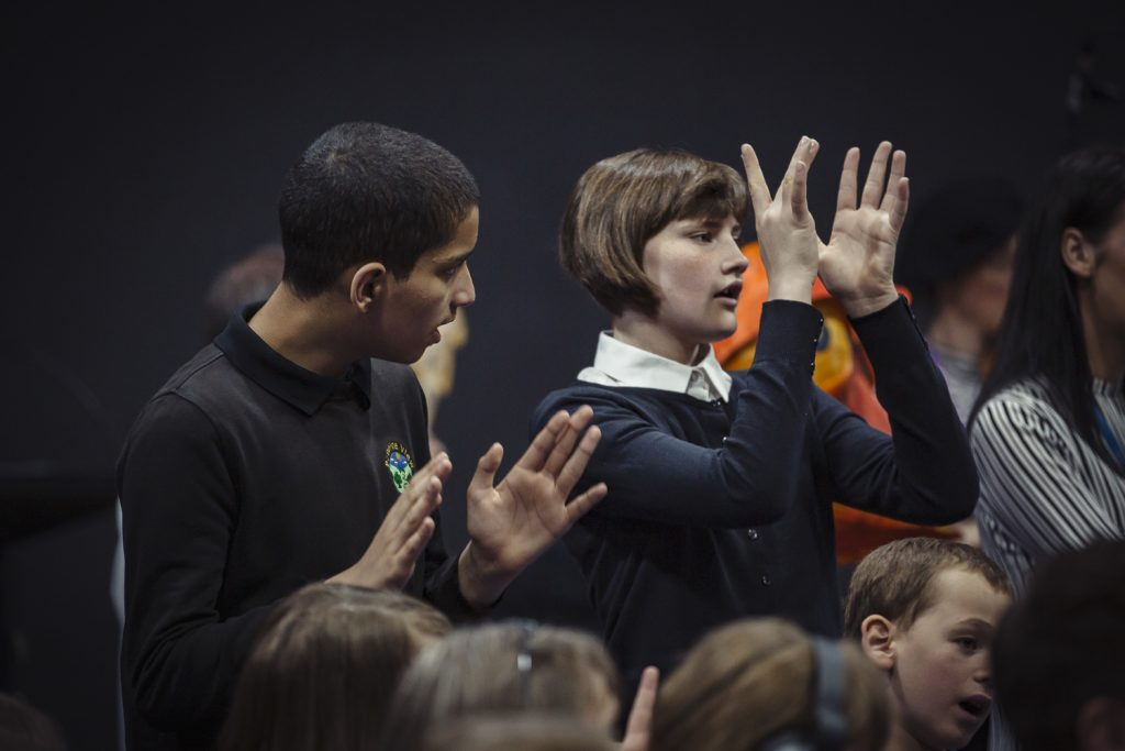 Young woman using Makaton sign language sings at a Sing and Sign performance in Doncaster