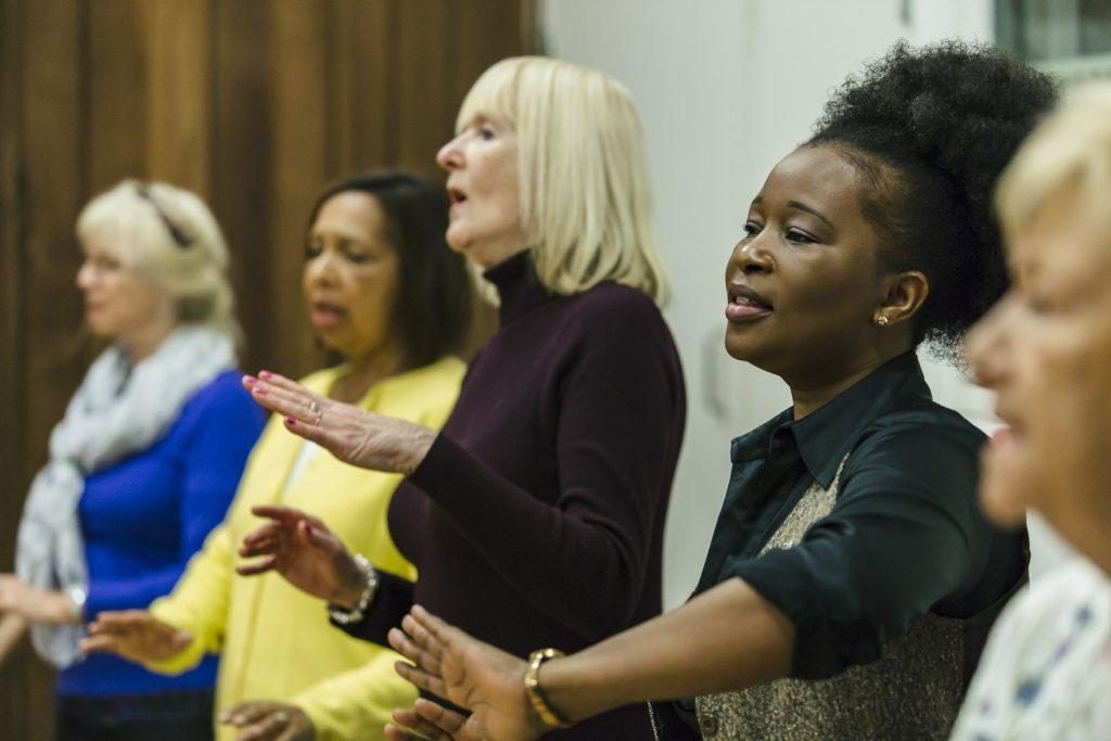 A group of women sing and smile as part of darts in Doncaster's Quirky Choir