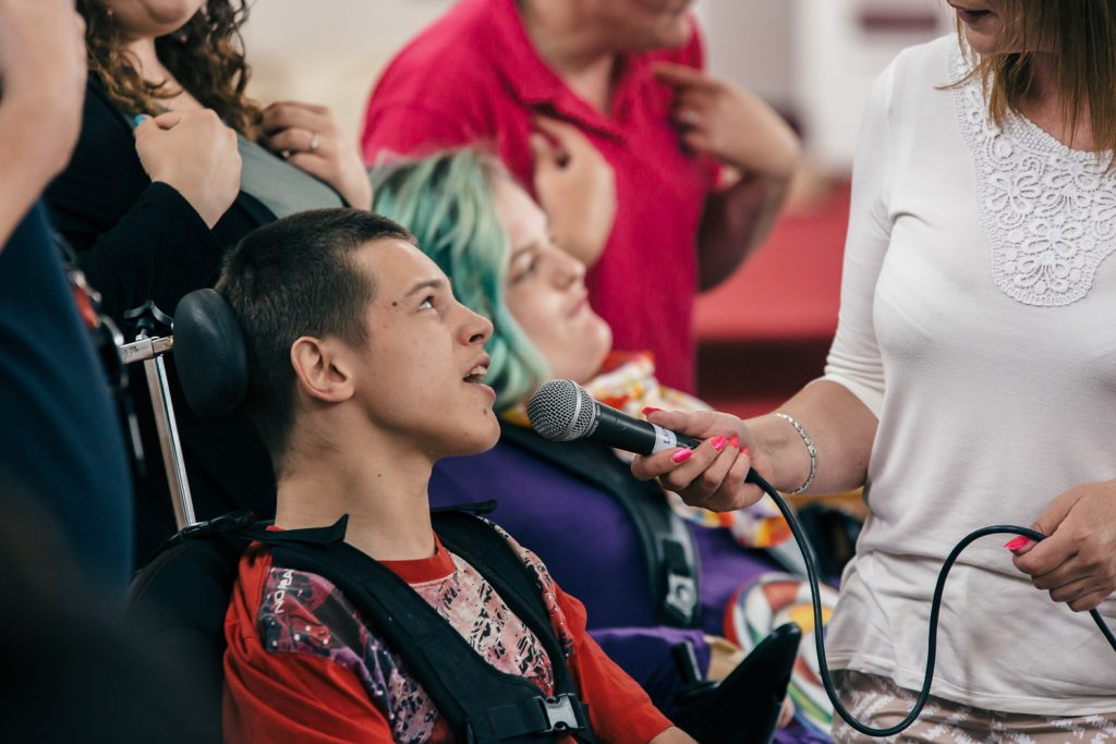 Young man in a wheelchair sings into a microphone at a We Speak Music event by darts in Doncaster