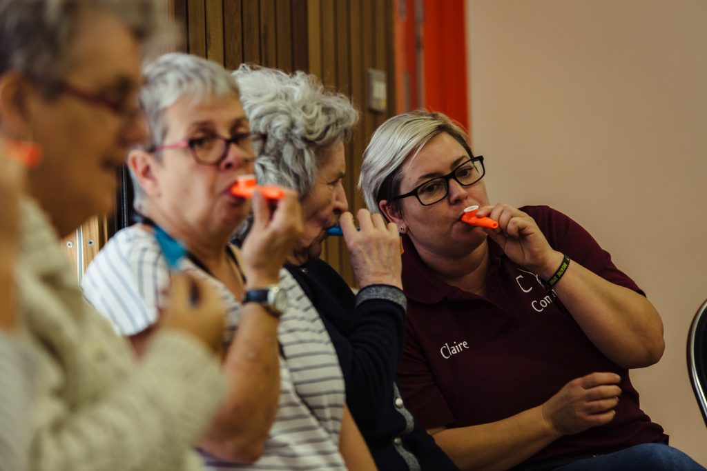 Older adults play kazoos at our Singing for Memory sessions for adults with dementia and their carers