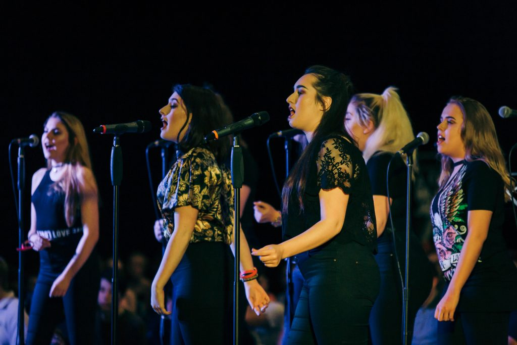 A group of teenage girls sing into microphones at a Music Hub event in Doncaster