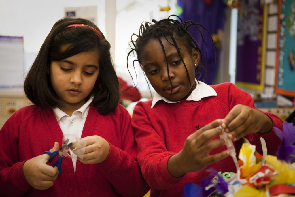 Two schoolchildren are immersed in making something with scissors and card