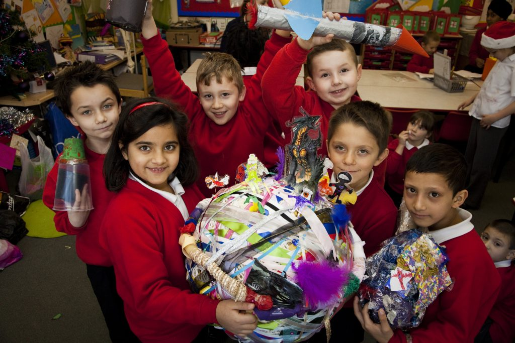 A group of schoolchildren smile at the camera and show off their artwork made with darts in Doncaster