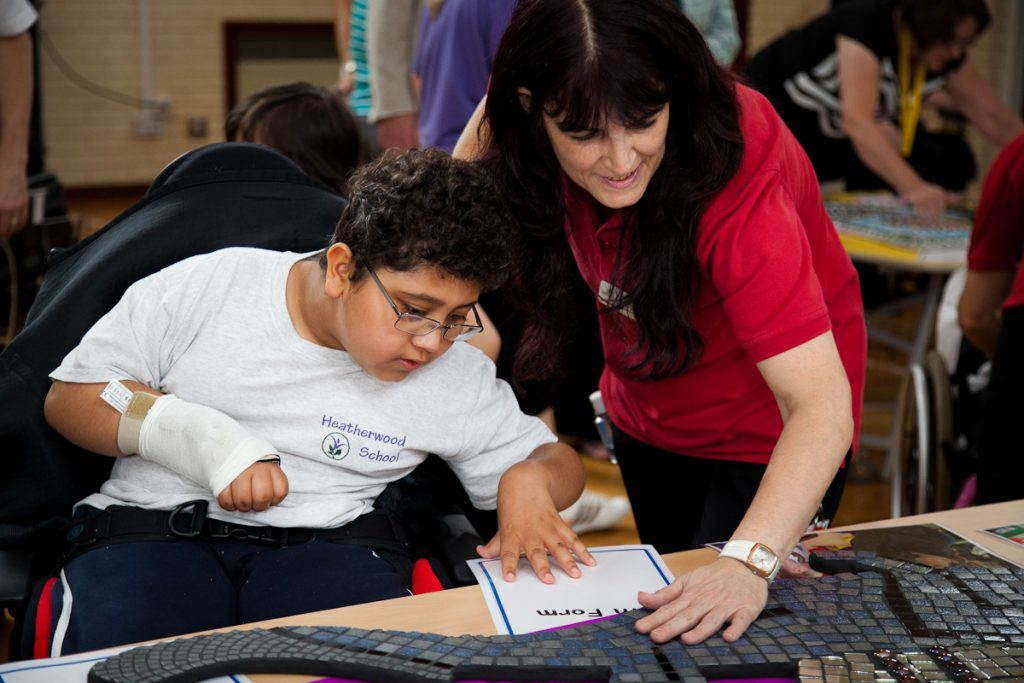 Young boy in a wheelchair doing an art project supported by a teacher - darts in Doncaster