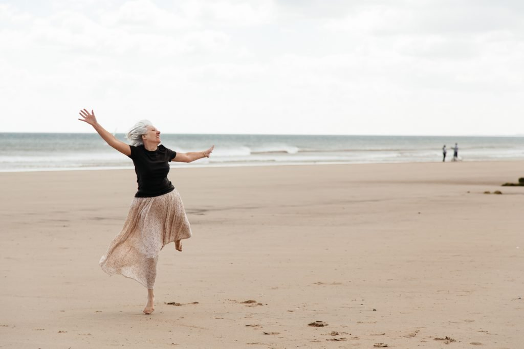 A lady dances freely on the beach as part of a film made by darts in Doncaster