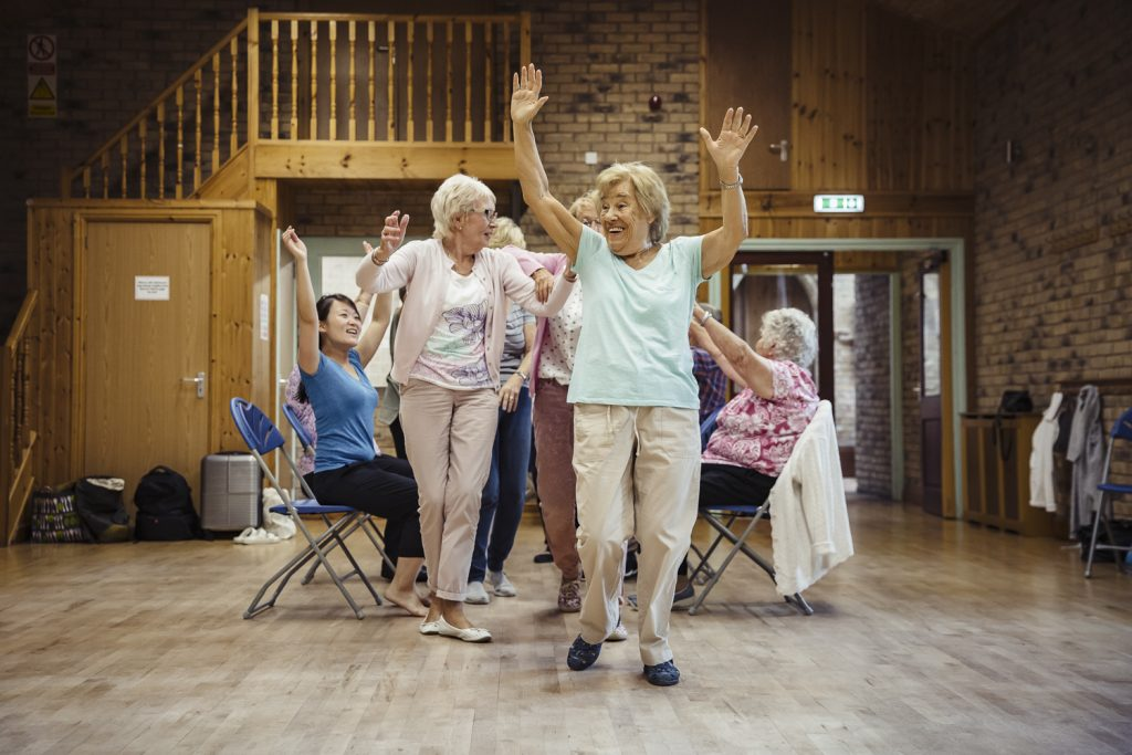 A group of women dancing at a Dance On session run by darts in Doncaster. Some have their arms in the air.
