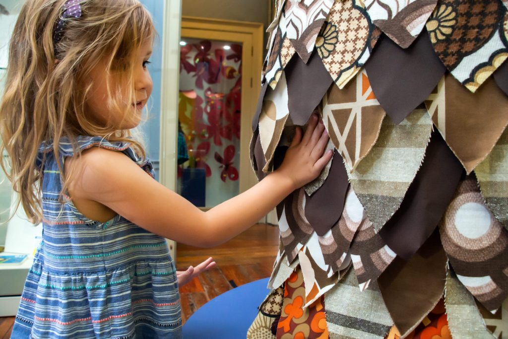 A girl pressing her hand onto an owl made of fabric at The Point in Doncaster.