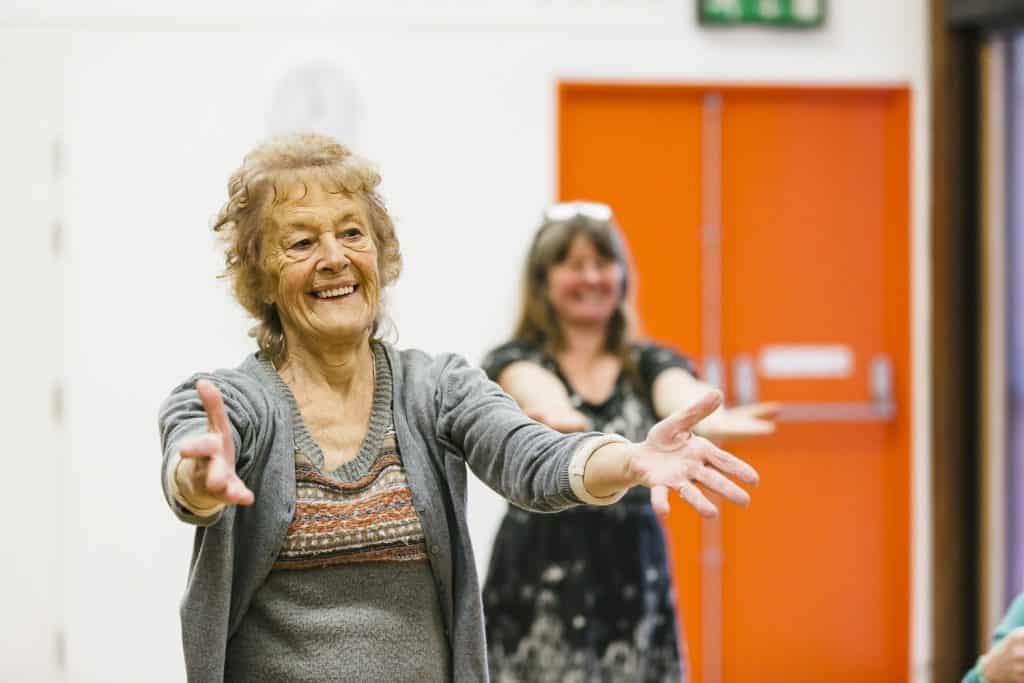 Two women stretching their arms out in Dance On with darts in Doncaster