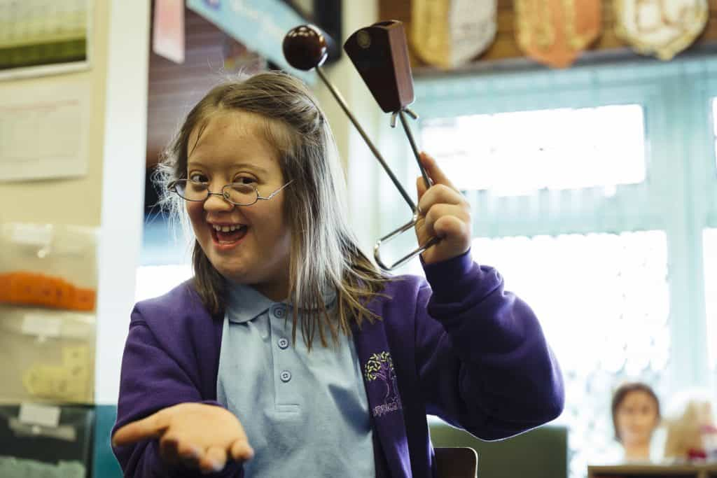 A girl from holding a percussion instrument in one darts' All Aboard sessions - The Point in Doncaster