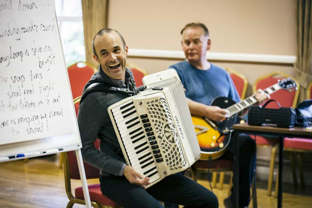 Luke Carver Goss plays his accordion and laughs, a man is playing his guitar