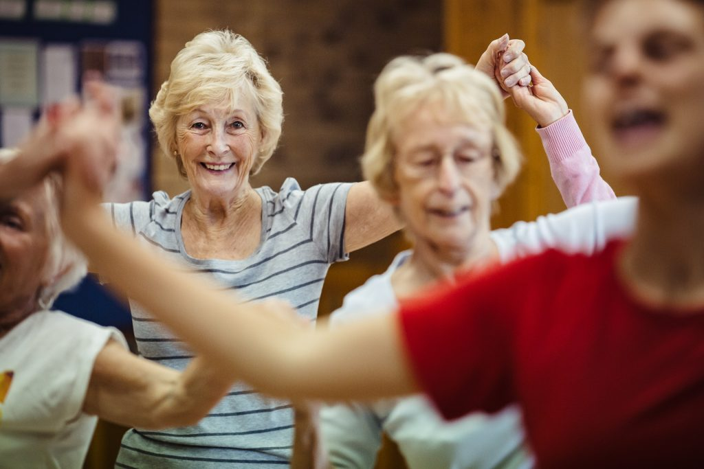 Two women laugh, smile and dance - Dance On project by darts in Doncaster