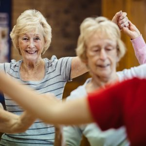 A small group of women dance and smile at a Dance On session with darts in Doncaster