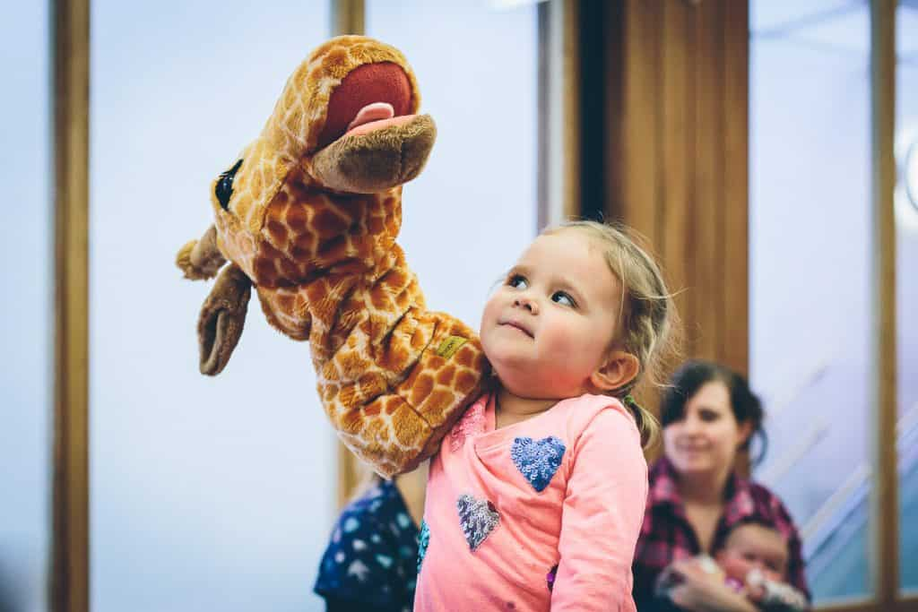 A young girl with her arm inside a giraffe hand puppet.
