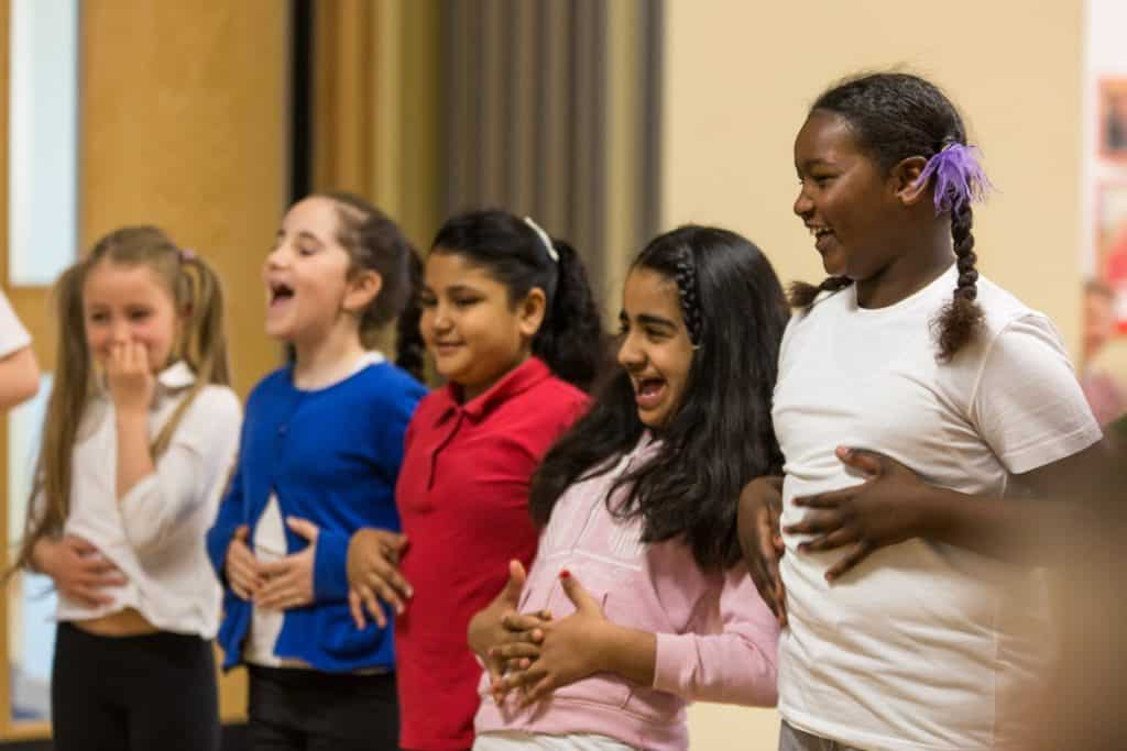 a group of children hold their stomachs and laugh as part of a drama and dance session by darts in Doncaster