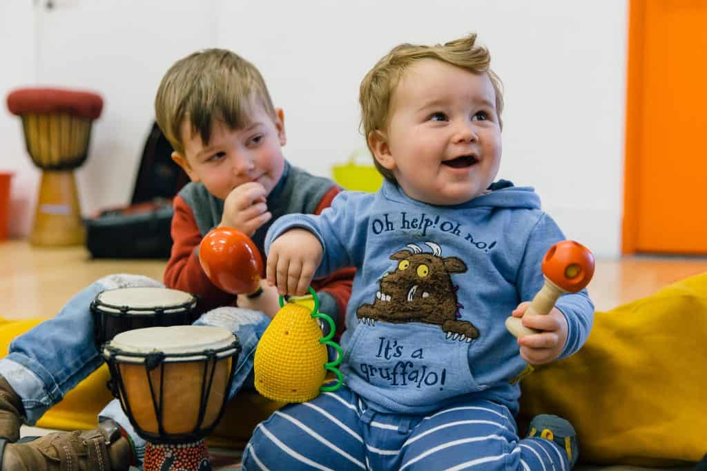Two toddlers smiling in a darts' Tuneful Chatter session.