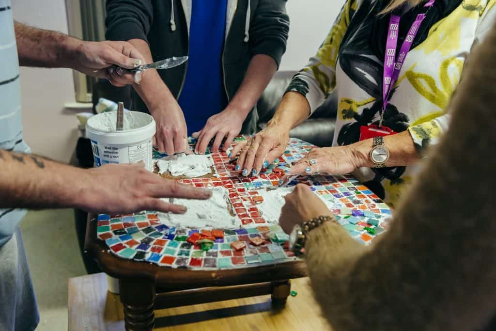lots of hands creating a mosaic at an approved premises with darts in Doncaster