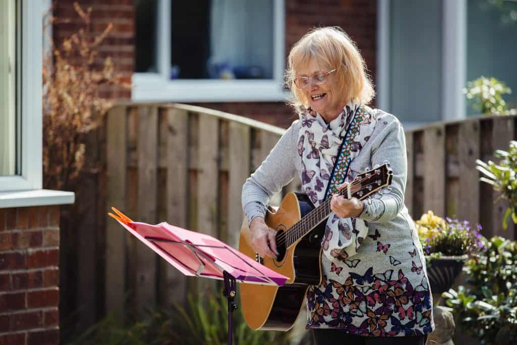 Musician Janet Wood playing the guitar at a darts Singing for Memory outdoor session.