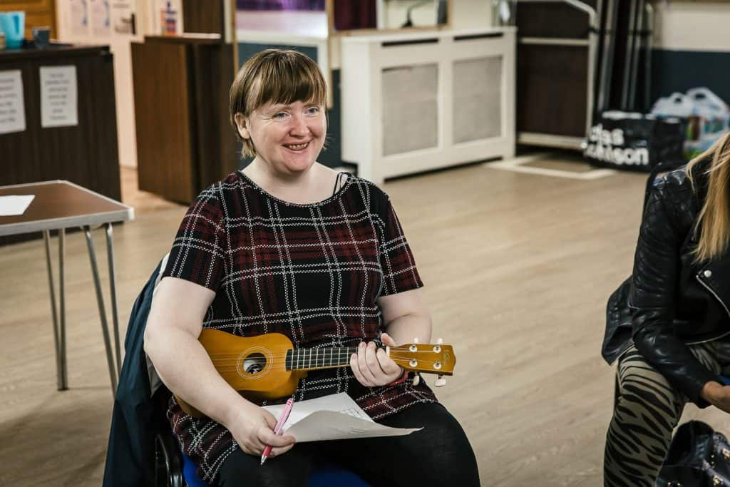 A woman smiling and holding a ukulele at a darts Creative Directions session in Edlington.
