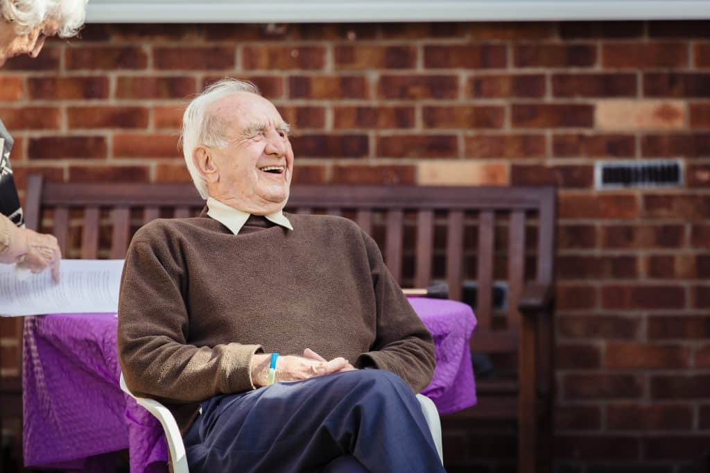 A man smiling and sat on a chair at a darts Singing for Memory session.