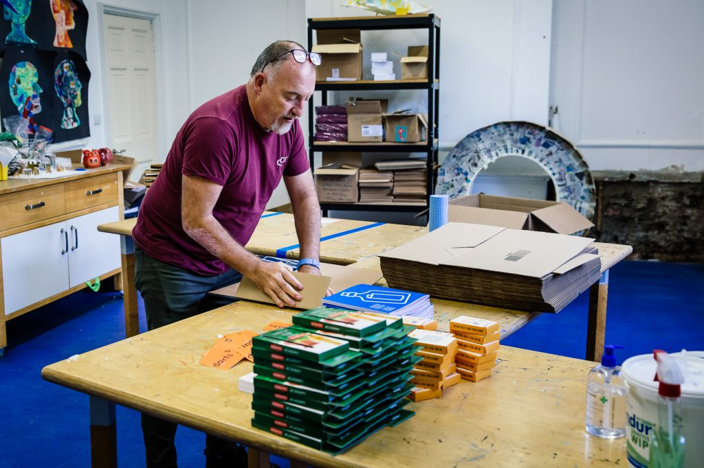 Jamie, a darts employee, packing some creative books at The Point in Doncaster.