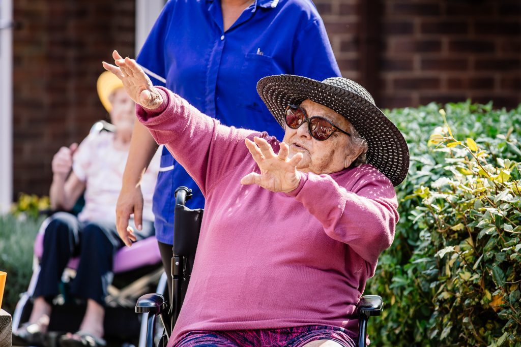 A woman in a hat and glasses dances with her arms in the air while sitting in a wheelchair at a dance session led by darts in Doncaster