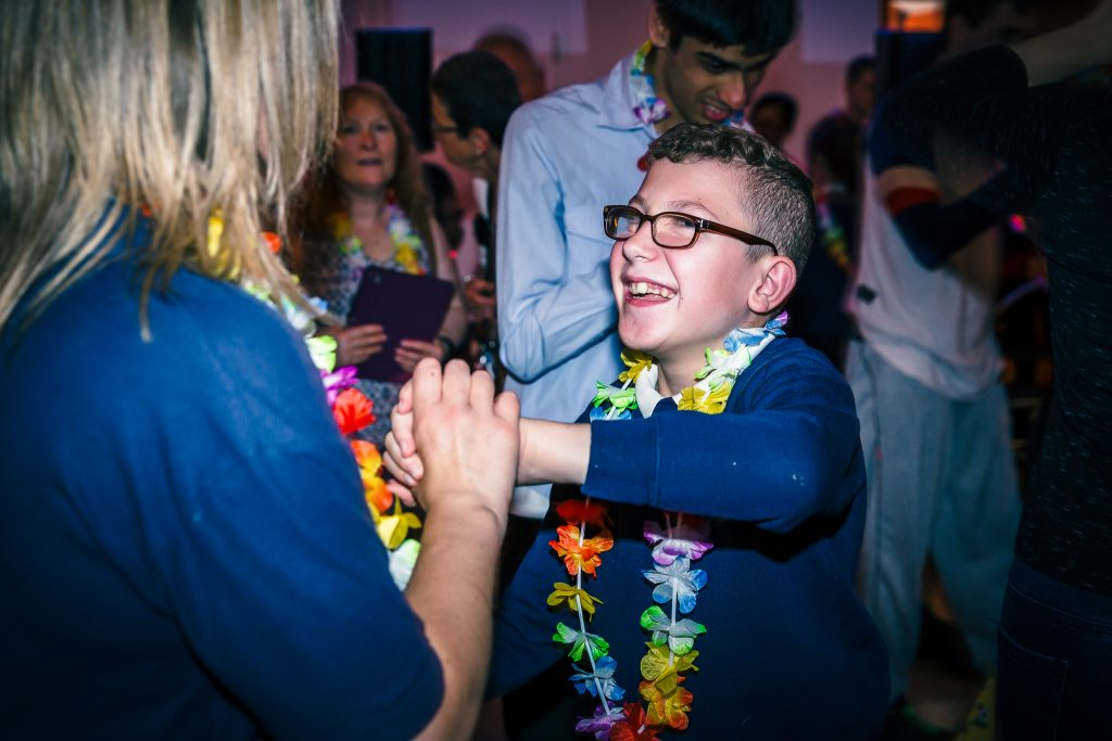 boy with glasses and a Hawaiian flower chain dances with a lady with long hair - darts in Doncaster