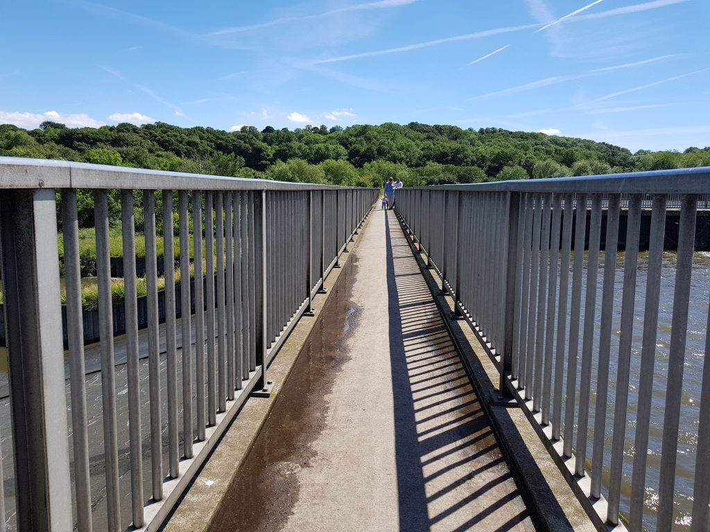 The view along a bridge with blue sky and green trees in the background - part of a film for darts in Doncaster