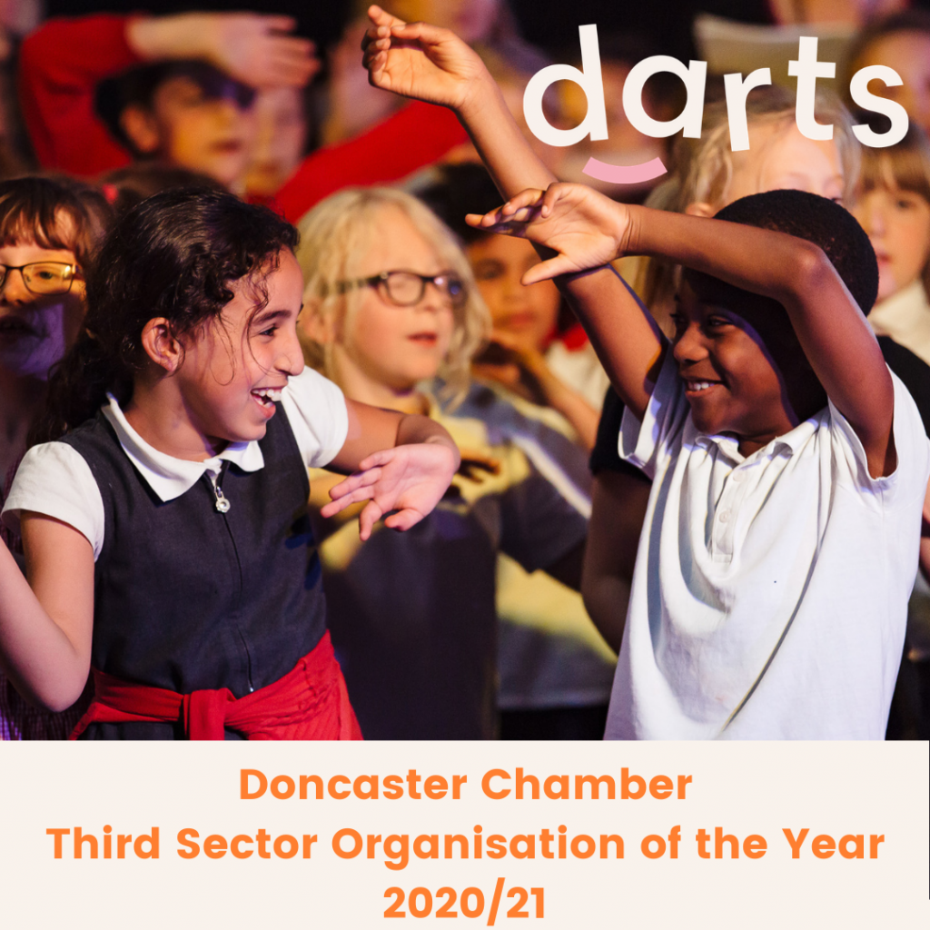 Two schoolchildren smile at each other and wave their arms at a music performance with darts - Doncaster Community Arts