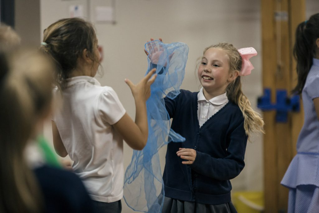 Two girls play with a blue scarf in a creative workshop in Doncaster