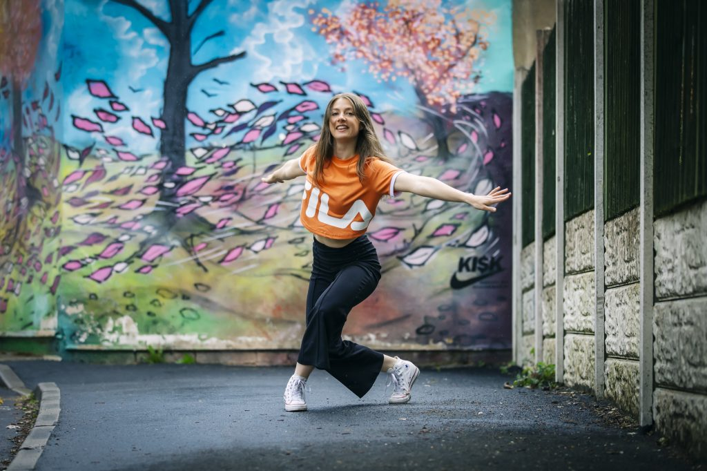 Woman in a bright orange t-shirt dances in front of a colourful mural