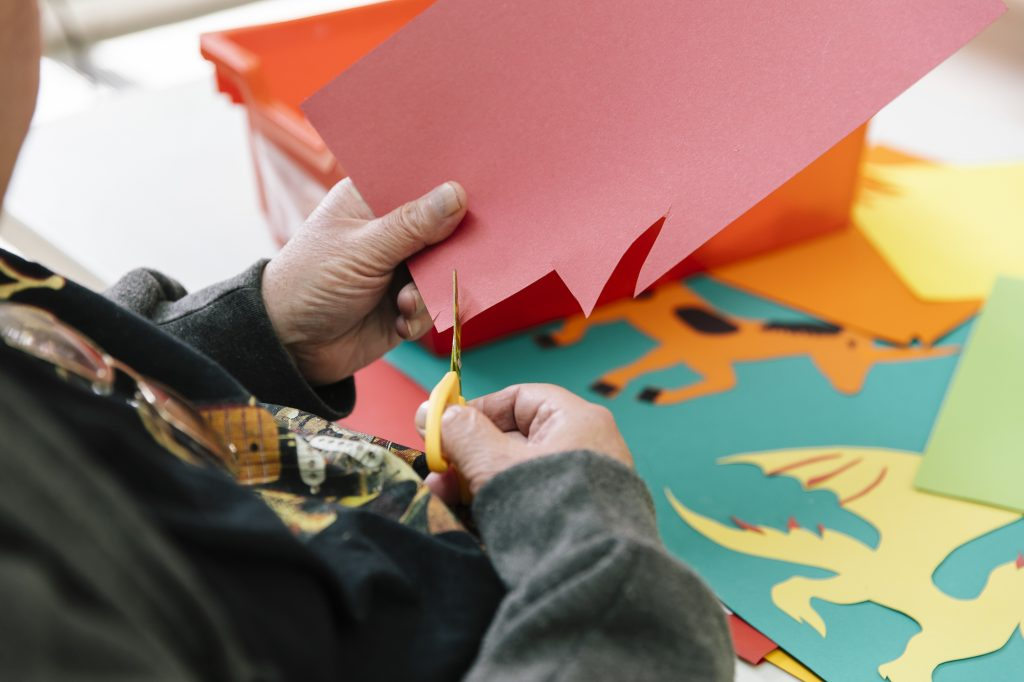 Man cuts shapes from red card with yellow scissors in a Creative Directions workshop at The Point in Doncaster