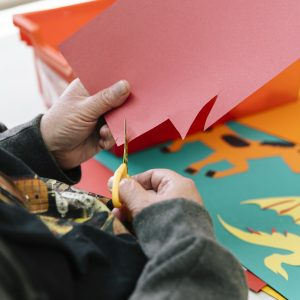 Close up of a man's hands cutting shapes out of piece of red card with yellow scissors