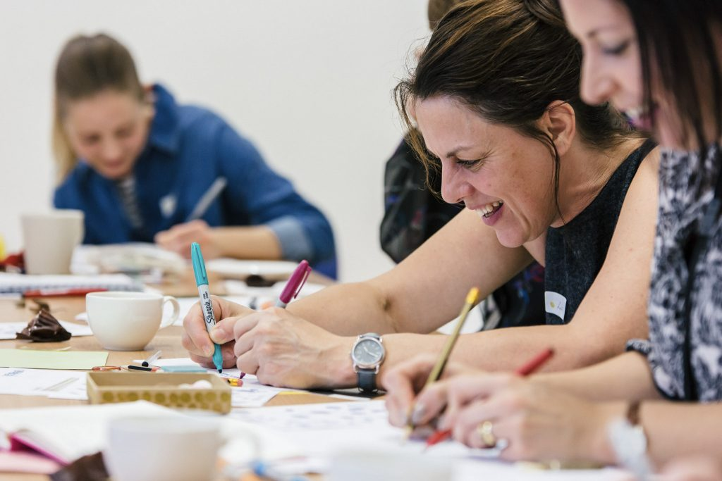 A group of women sitting around a table draw using pens and pencils in a teacher training session at The Point in Doncaster