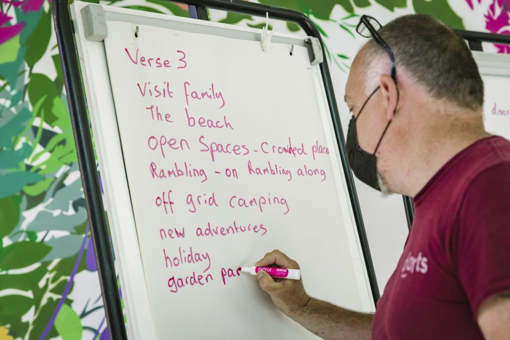 A man wearing a face covering writes ideas for song lyrics on a flip chart with a pink marker pen. Part of a Creative Directions in the Community workshop with darts in Doncaster.