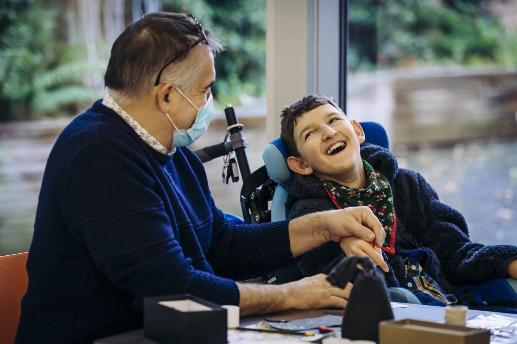 A young person in a wheelchair and his dad enjoy an All Aboard Christmas workshop at The Point with darts in Doncaster